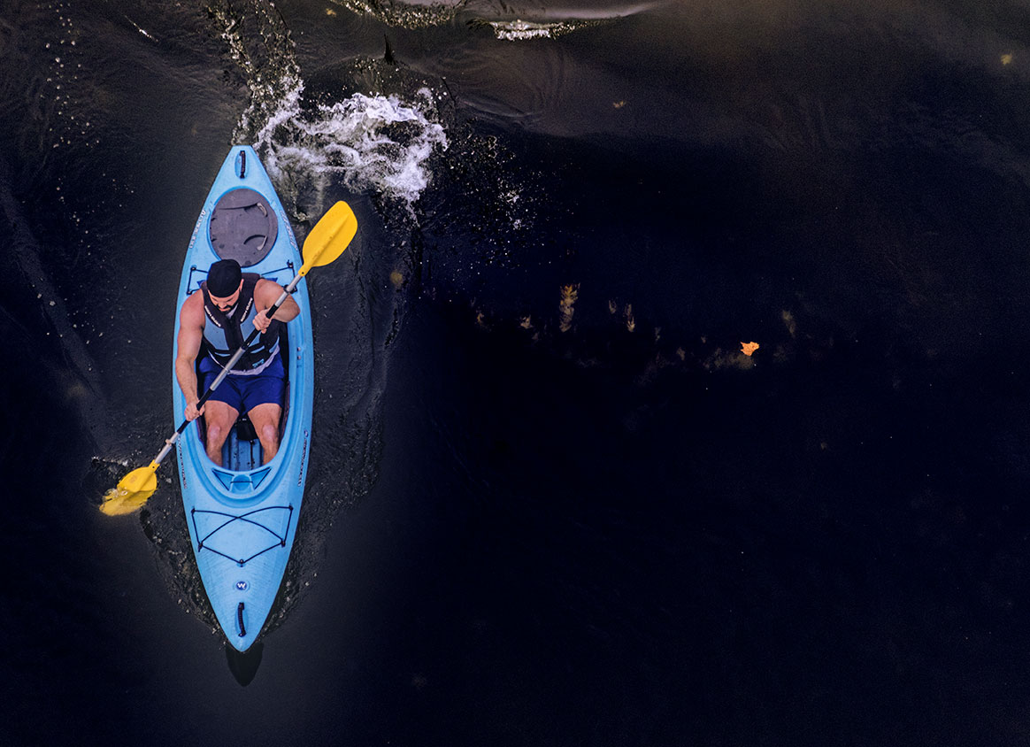 blue kayak is paddled by male down Levisa Fork River